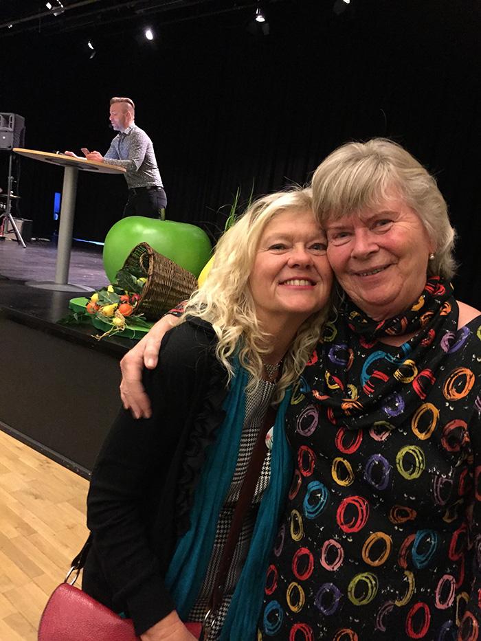 Två glada kvinnor håller om varandra, i bakgrunden en ung man på scenen