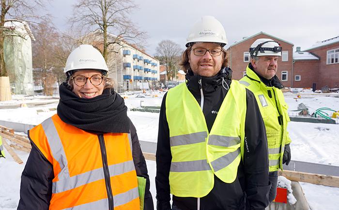 Kvinna och tre män vid byggarbetsplats, med hjälmar och skyddsvästar