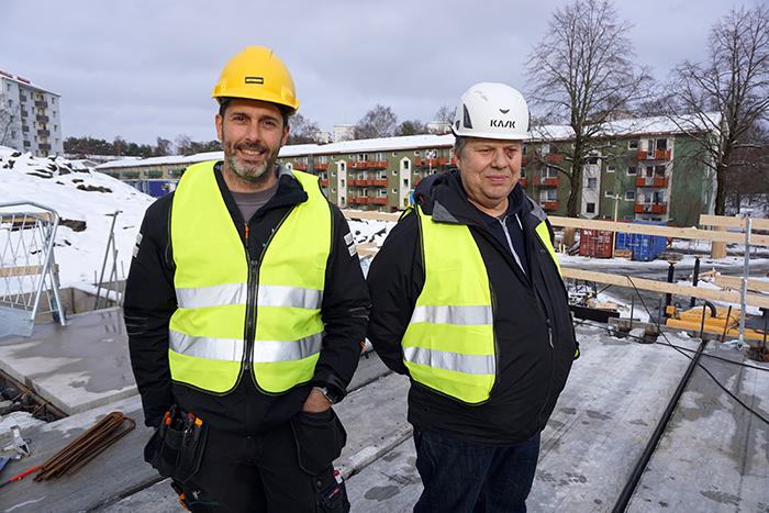 Två glada män med hjälmar och skyddsvästar på taket till det nybyggda parkeringsgaraget
