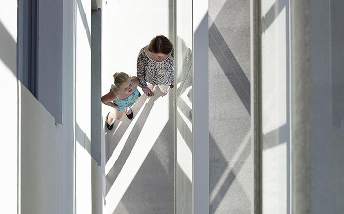 Detaljbild från hus, tagen uppifrån med två personer genom balkar och glas