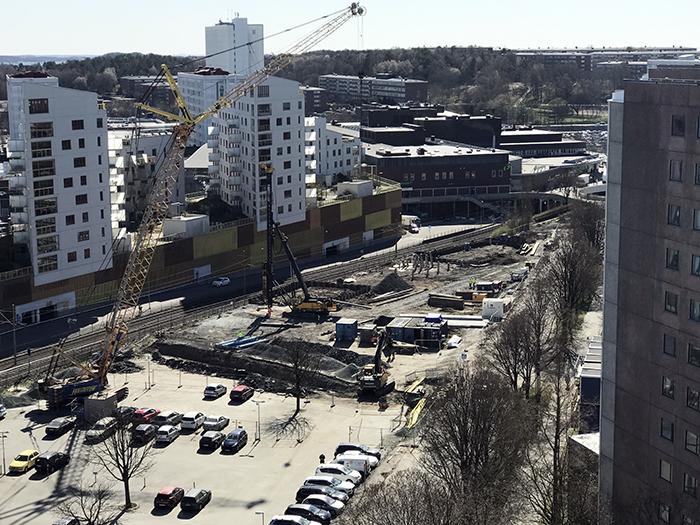 Byggarbetsplats i släpljus, stora vita hus i bakgrunden