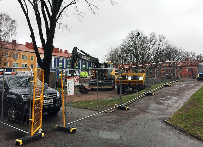 Staket, bil och grävskopa på gården intill husen som ska byggas till och om