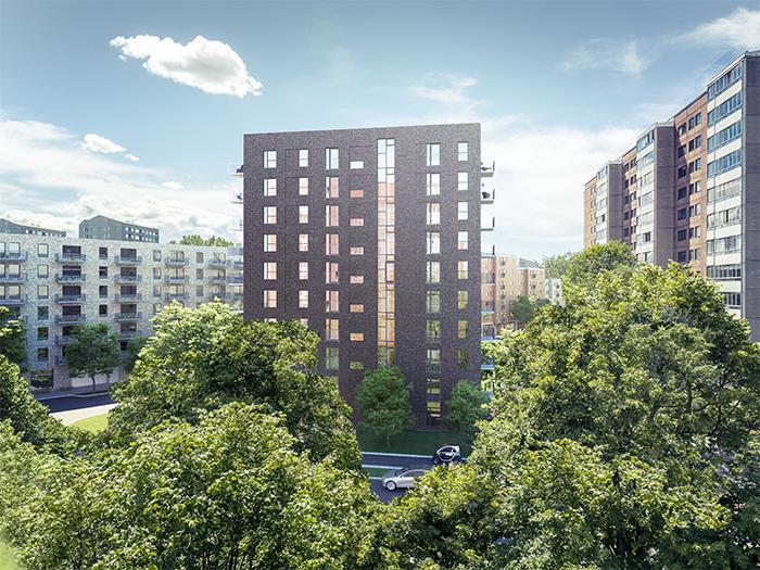 Ett nybyggt tegelhus i rödbrun ton bland träd och befintlig bebyggelse