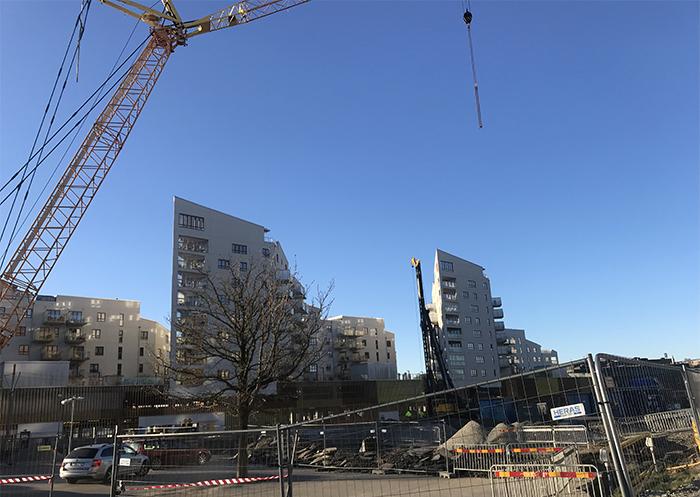 Byggarbetsplats, blå himmel, byggkran och vita höghus i bakgrunden
